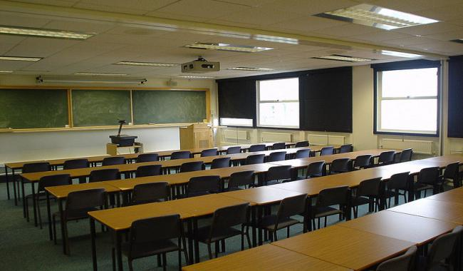 An empty classroom with rows of desk and chairs.