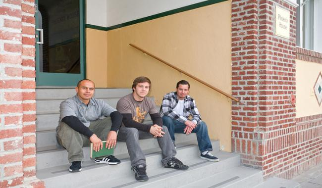 3 males sitting on the steps of a building
