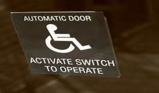 """An image of push button with universal access symbol that reads """"activate switch to operate"""" to open door"""