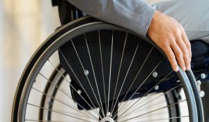 An image of hand on wheel of a wheelchair