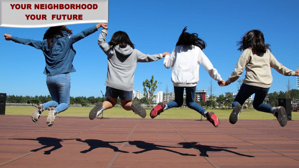 """Color photo of four girls jumping into the air at a park. """"Your neighborhood, your future"""" is displayed in the upper left corner."""