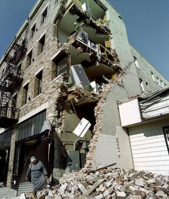 Woman standing in front of earthquake-damaged apartment building